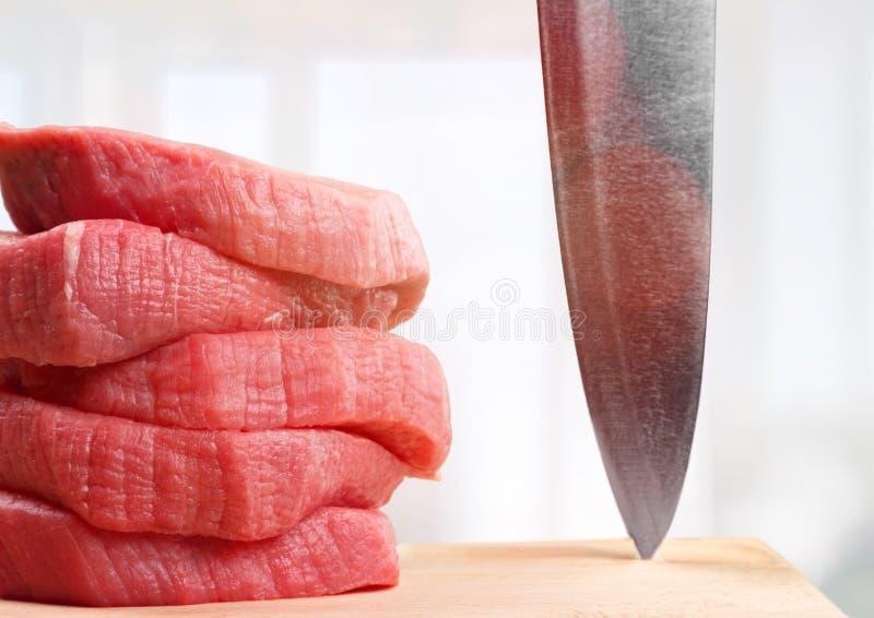 Fatias e faca da carne crua na placa de corte fotos de stock