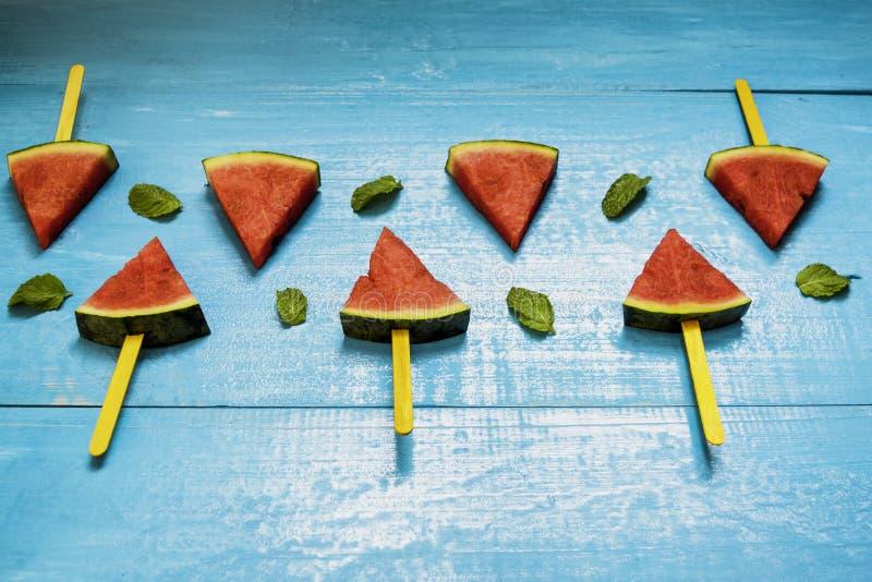 Fatias e hortelã da melancia no fundo de madeira azul brilhante, fruto orgânico do conceito não-tóxico para a saúde, para o refre imagem de stock royalty free