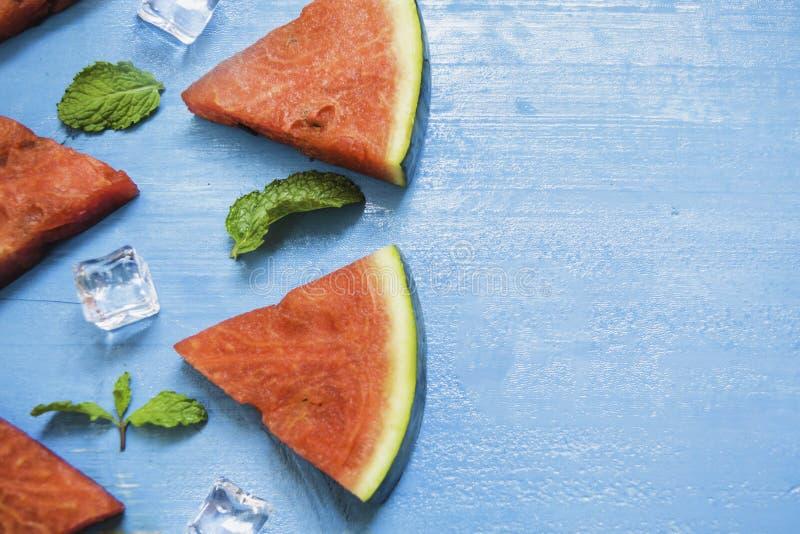 Fatias e hortelã da melancia no fundo de madeira brilhante e de gelo do azul, fruto orgânico do conceito não-tóxico para a saúde, fotos de stock royalty free
