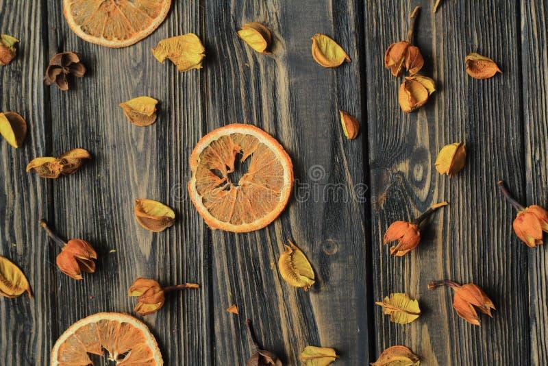 Fatias e pétalas alaranjadas de flores secadas no fundo de madeira imagem de stock