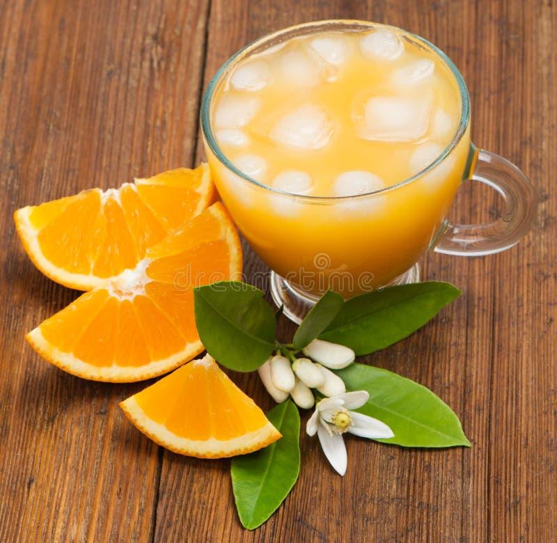 Fatias e suco de laranja alaranjados imagem de stock royalty free