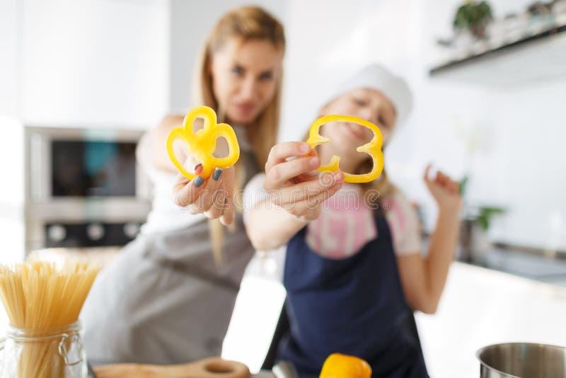 Fatias felizes da pimenta da posse da mãe e da filha na sala da cozinha O processo de cozinhar um prato saudável dos vegetais foto de stock