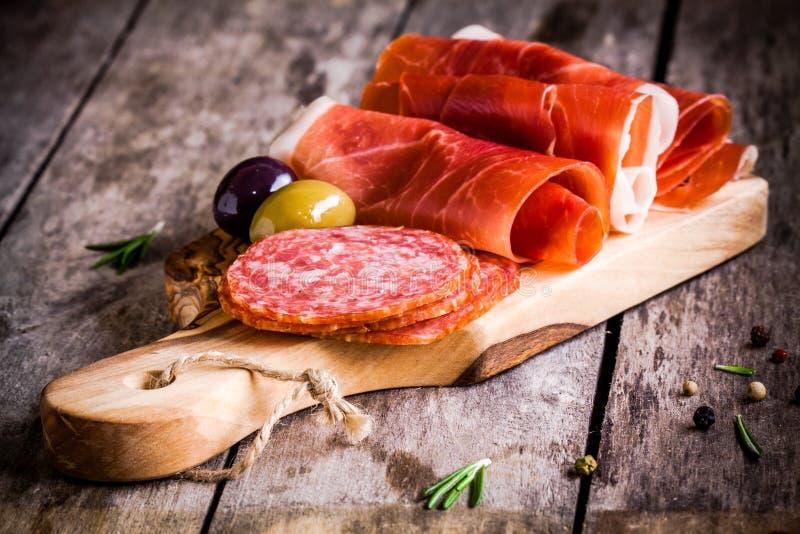 Fatias finas de prosciutto com salame, azeitonas e alecrins em uma placa de corte fotos de stock royalty free