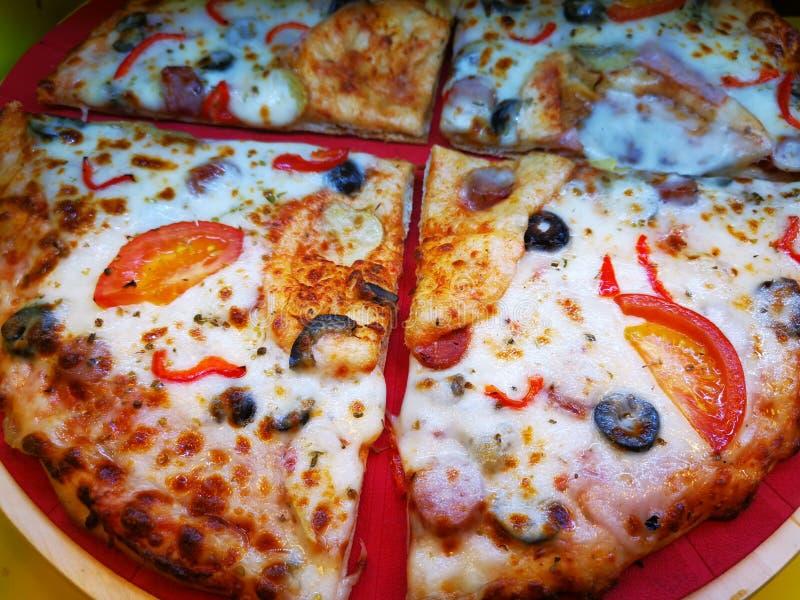 Fatias frescas da pizza em fatias dianteiras e mais velhas na parte traseira foto de stock royalty free