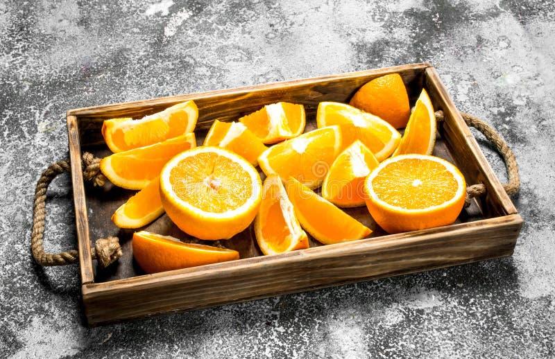 Fatias frescas de laranjas em uma bandeja de madeira imagem de stock