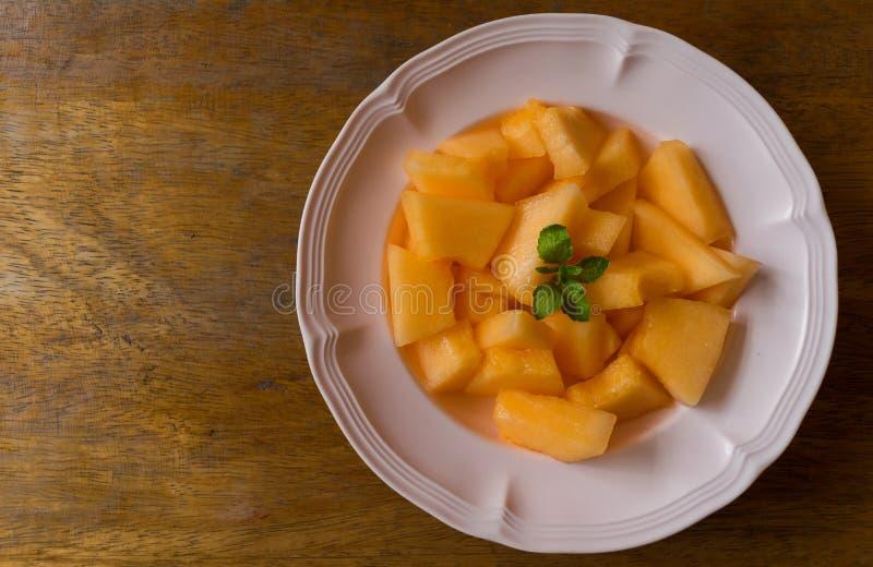 Fatias frescas do cantalupo em um prato imagem de stock