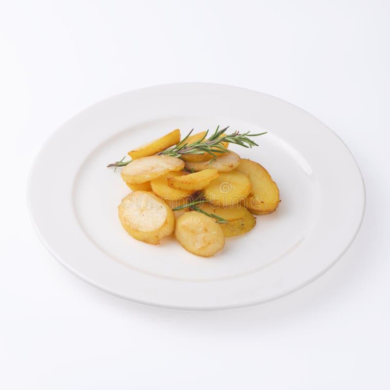 Fatias fritadas crocantes da batata com os alecrins frescos isolados no fundo branco fotos de stock royalty free