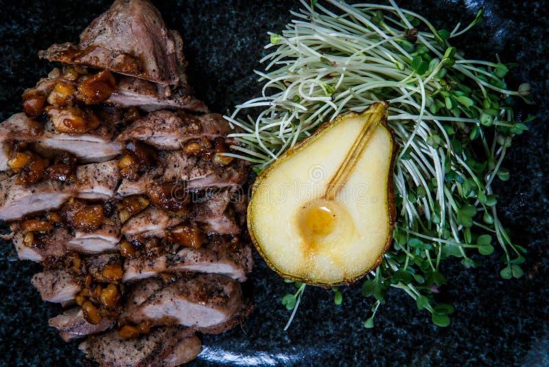 fatias roasted macro da carne da vista superior com metade da pera grelhada imagens de stock royalty free