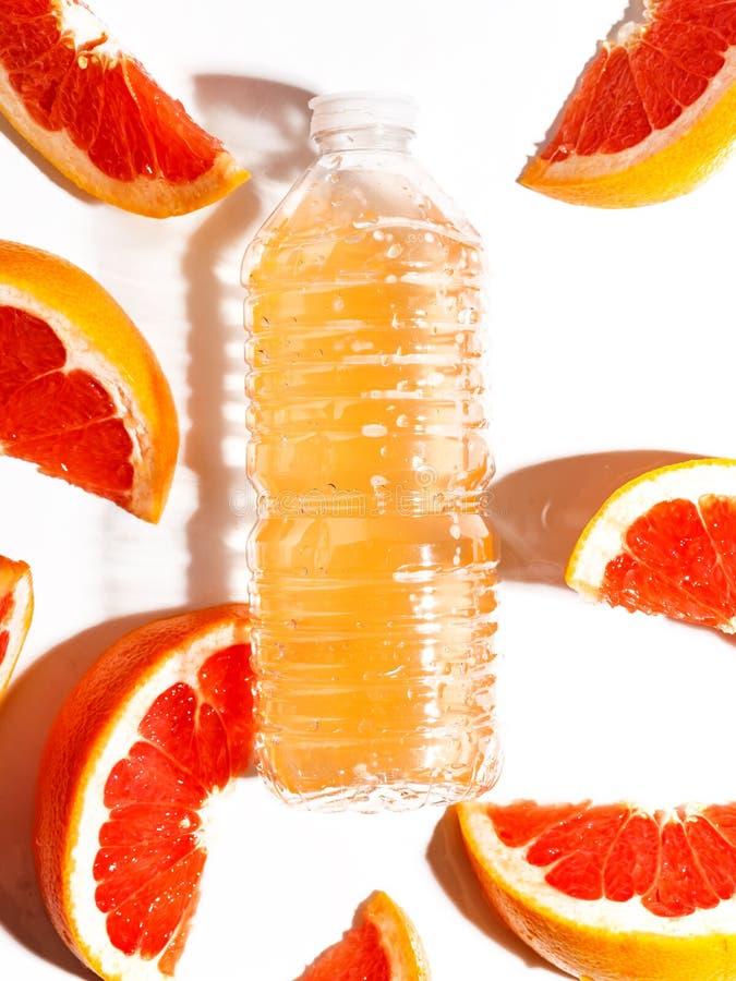 Fatias suculentas da toranja e uma garrafa com suco em um fundo branco Vista superior fotografia de stock royalty free