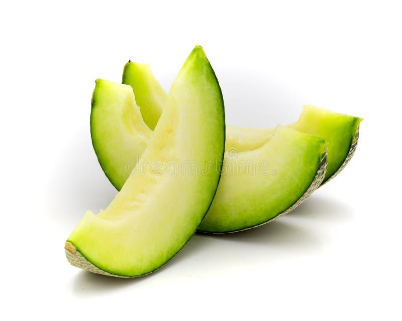 Fatias verdes do melão isoladas no fundo branco imagem de stock royalty free