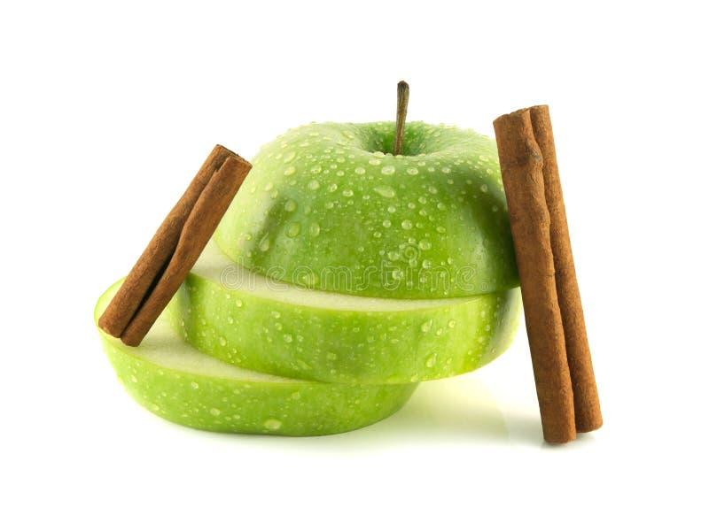 Fatias verdes isoladas da maçã com vagens da canela imagem de stock