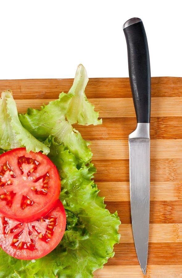 Fatias vermelhas do tomate, folhas da salada e uma faca imagem de stock royalty free