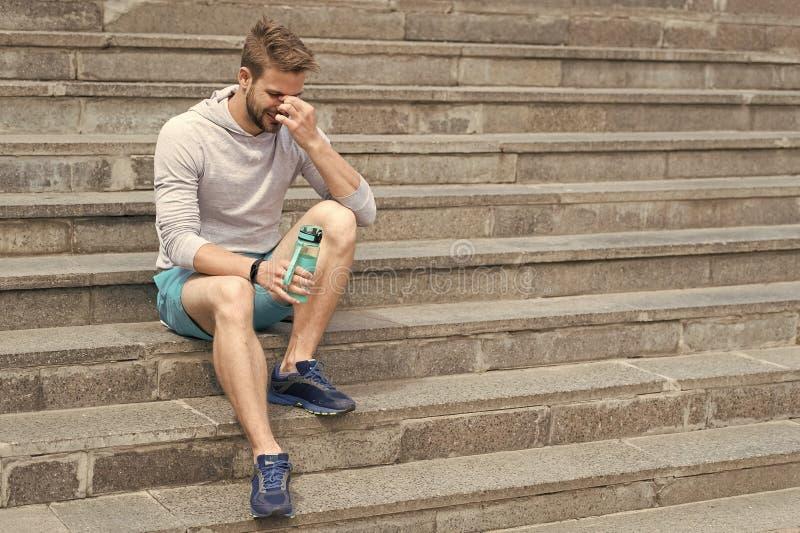 Fatigué après la formation sur l'air frais Séjour hydraté et sain Le macho avec la bouteille d'eau s'asseyent sur des étapes, cop image libre de droits