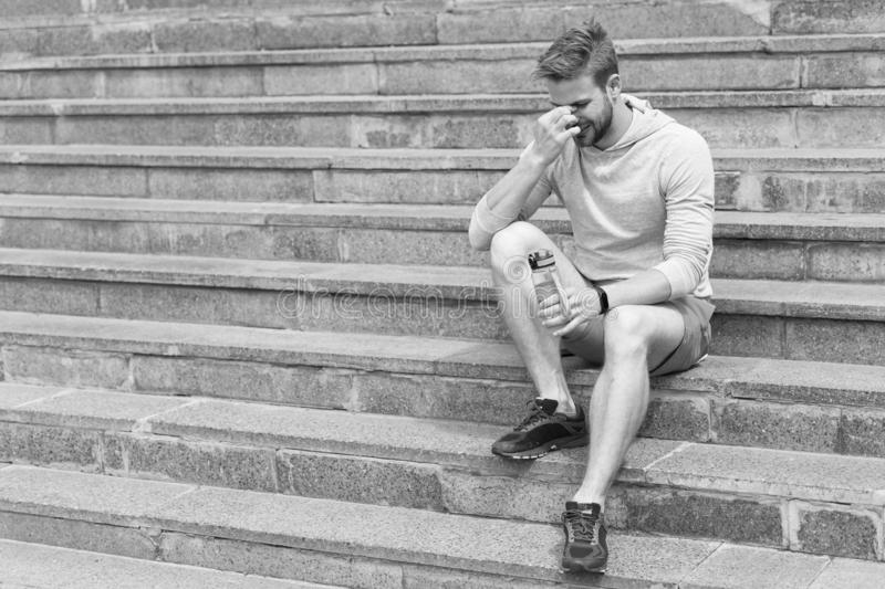 Fatigué après la formation sur l'air frais Séjour hydraté et sain Le macho avec la bouteille d'eau s'asseyent sur des étapes, cop photo libre de droits