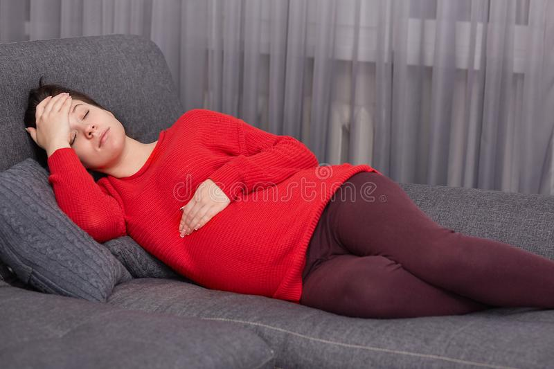 Fatigue European young woman keeps one hand on stomach and other on forehead, lies on comfortable sofa, rests at home, needs good royalty free stock photo