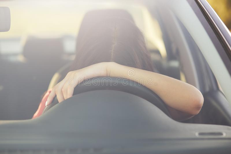 Fatigue sleepless female driver leans on wheel, stops to have rest, poses in car, covered long distance during night, feels tired. stock image