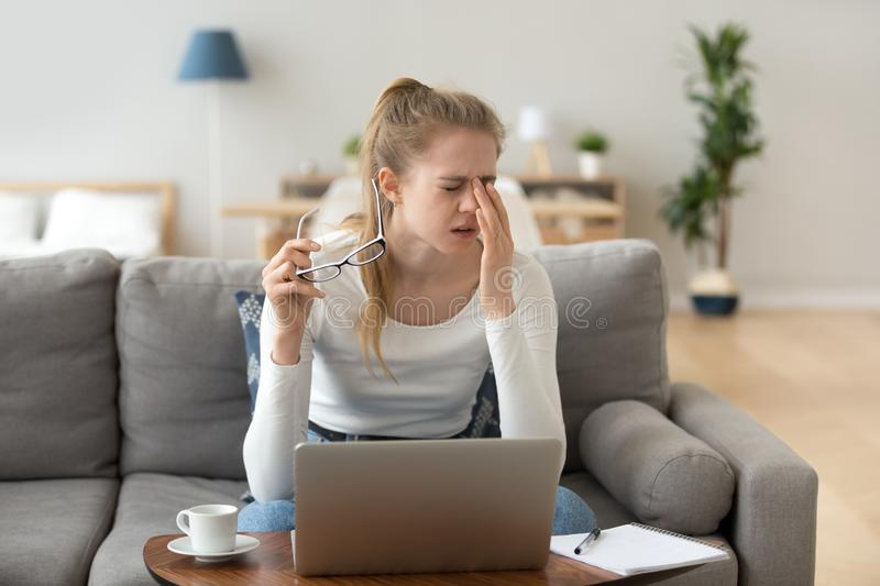 Fatigued woman feels eye strain rubbing eyes taking off glasses. Fatigued young woman feels eye strain rubbing dry irritated eyes taking off glasses after stock images