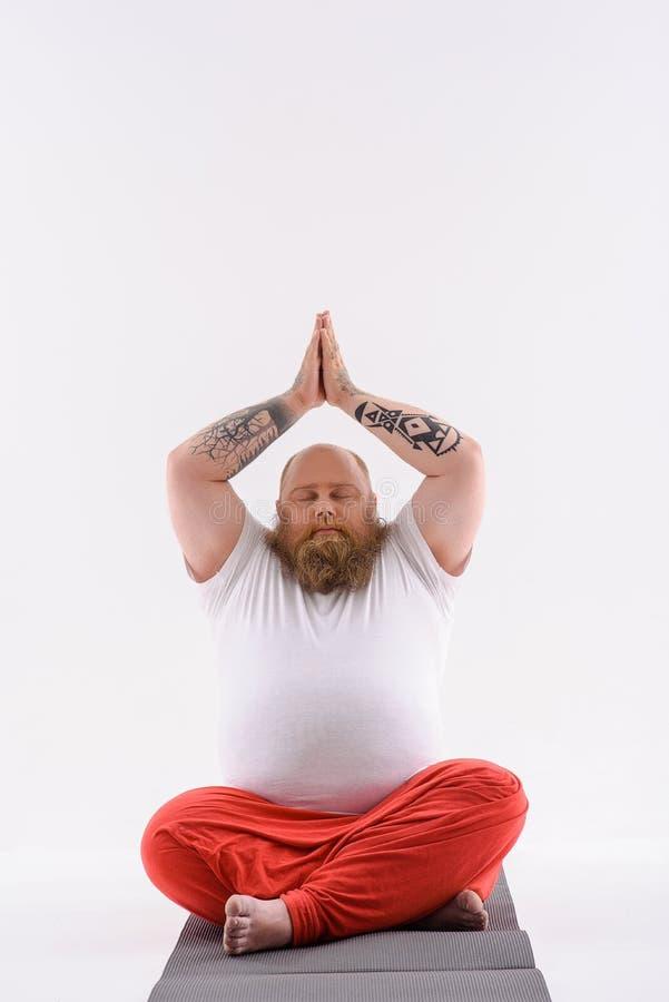 Fatso masculino que medita sobre a esteira imagens de stock royalty free