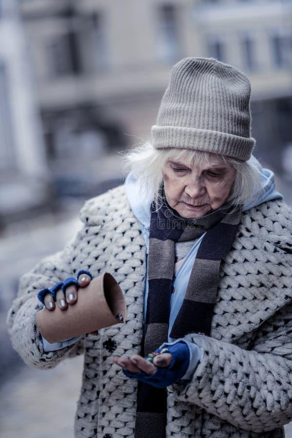 Fattig åldrig kvinna som önskar att äta något arkivfoto