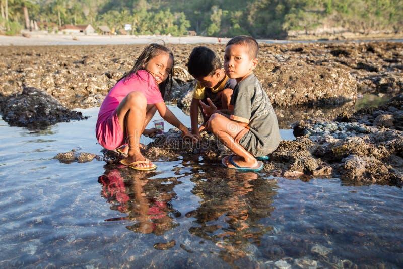 Fattig barnlek på stranden i u-land arkivbild