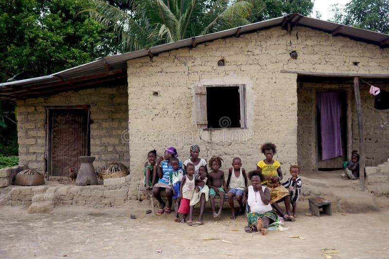 Fattig familj utanför deras hus i Sierra Leone, Afrika royaltyfri foto