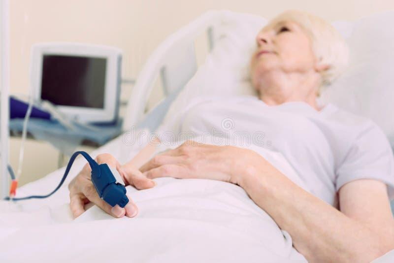 Fattig hög dam som ligger i sjukhussäng med pulsoximeteren royaltyfria bilder
