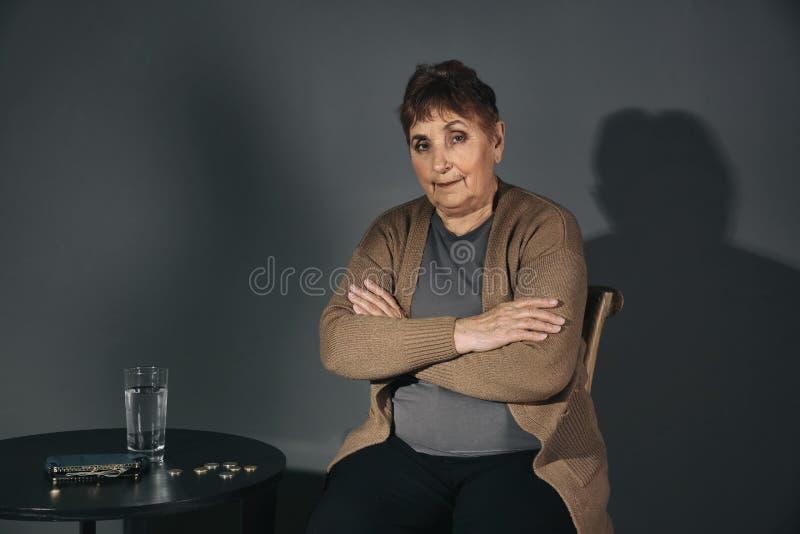 Fattig hög kvinna med vatten och mynt på tabellen på grå bakgrund royaltyfria bilder