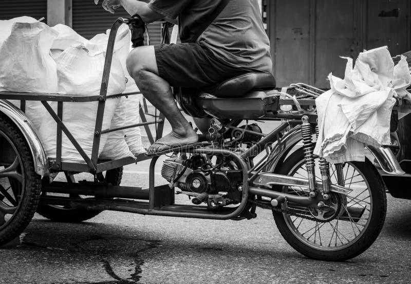 Fattig hög man som kör en moped som överför ispåsen till en restaurang Det äldre folket arbetar efter avgång Avgångpengar royaltyfria bilder
