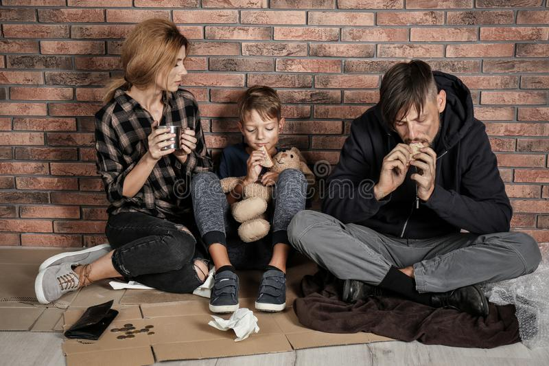 Fattig hemlös familj som sitter på golv royaltyfria bilder