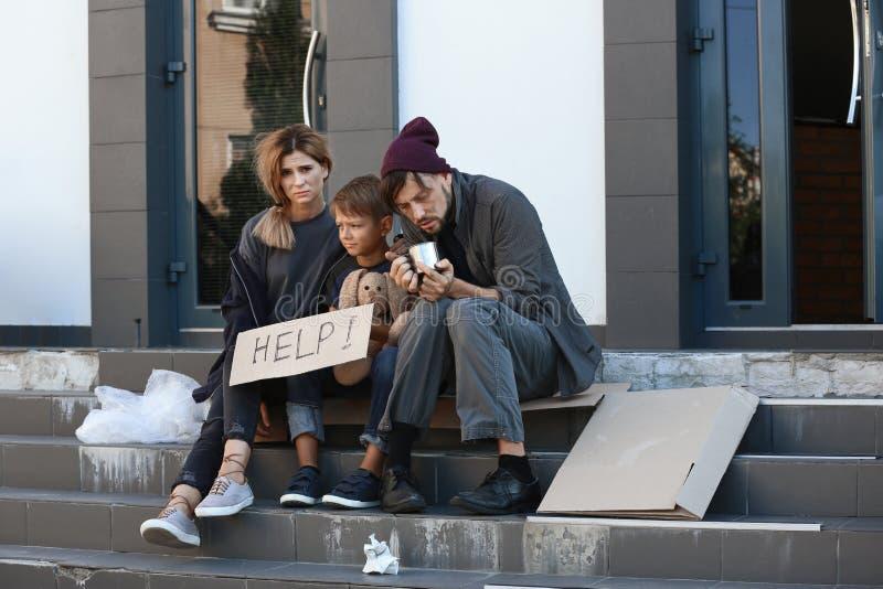 Fattig hemlös familj som tigger och frågar för hjälp arkivfoto