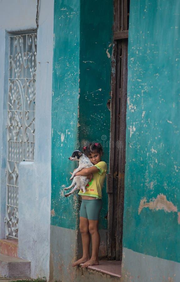 Fattig kubansk flickatillfångatagandestående i traditionell färgrik kolonial gränd med gammal livstil, i gammal stad, Kuba, Ameri arkivbild