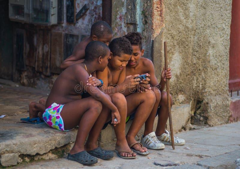 Fattig kubansk pojketillfångatagandestående i traditionell kolonial gränd med gammal livstil, i gammal havannacigarr, Kuba, Ameri royaltyfri bild