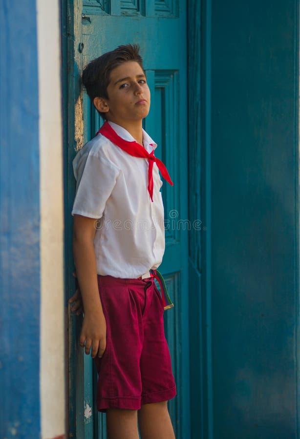 Fattig kubansk studenttillfångatagandestående i traditionell kolonial gränd med det röda ärret, i gammal havannacigarr, Kuba, Ame arkivbilder