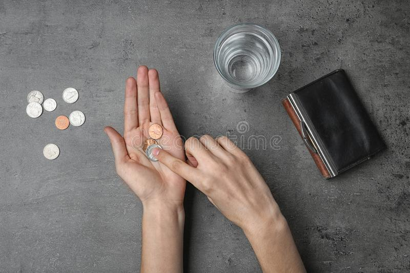 Fattig kvinna som räknar mynt på grå bakgrund, bästa sikt fotografering för bildbyråer