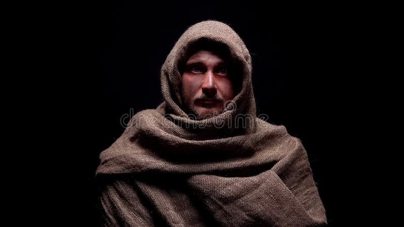 Fattig man i den grova ämbetsdräkten som ser direkt till kameran, tidig kristen profet arkivfoto