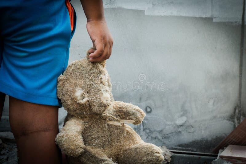 Fattig pojke som rymmer en nallebjörn royaltyfri bild