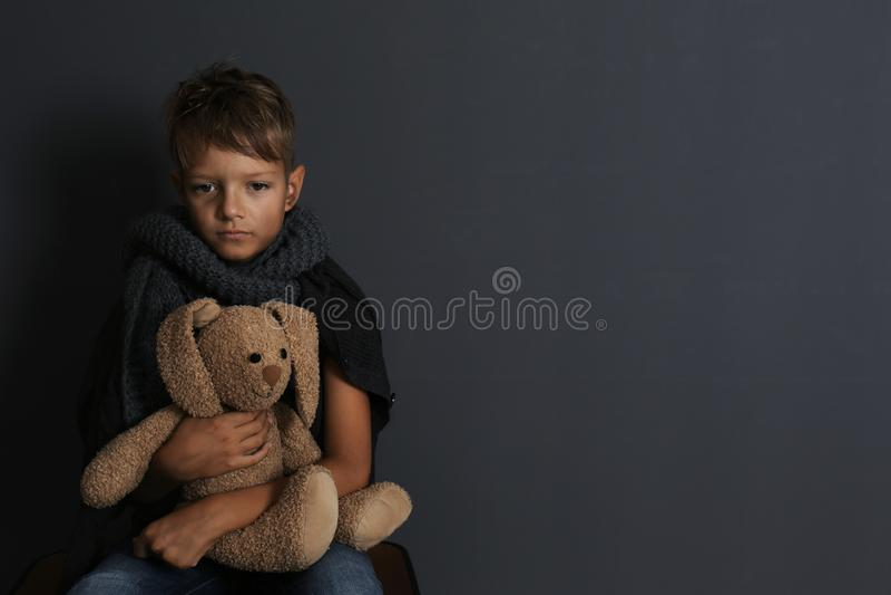 Fattig pojke som sitter med leksakkanin på mörk bakgrund royaltyfri foto