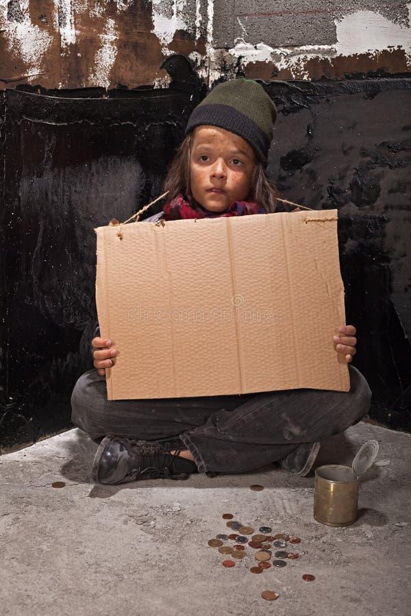 Fattig tiggarepojke på gatan med ett papptecken royaltyfri foto