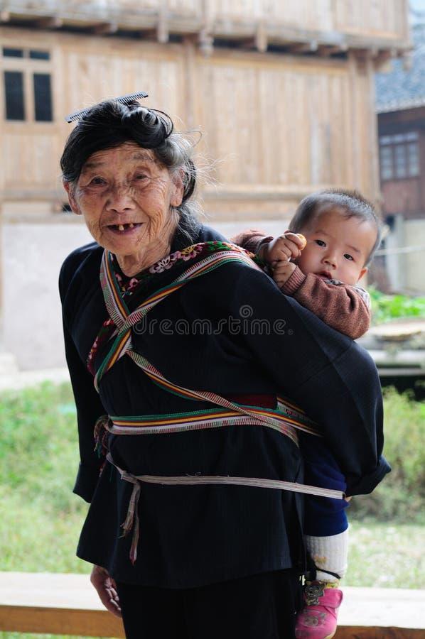 Fattig traditionell dam som att bry sig ungen i den gamla byn i Kina arkivfoto