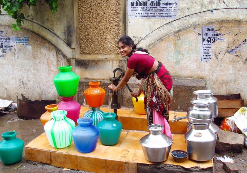 Fattig ung indisk kvinna i en sari med färgrika krukor nära vattenkällan arkivfoto