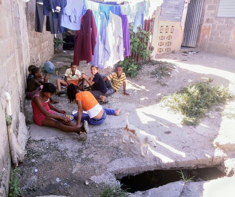 Fattiga barn som spelar på jordningen bredvid en outfall royaltyfria bilder