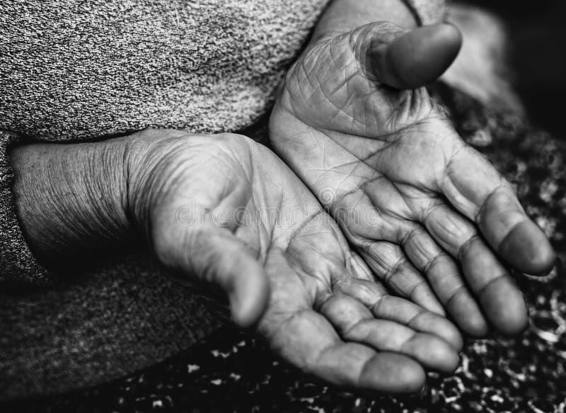 Fattiga gamla händer av den hemlösa tiggaren arkivfoto
