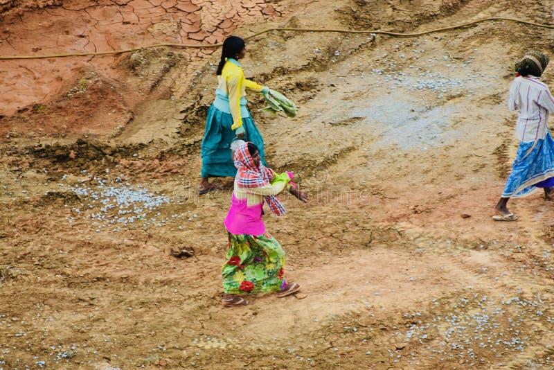 Fattiga indiska kvinnaarbetare som går till och med en konstruktionsplats arkivfoton