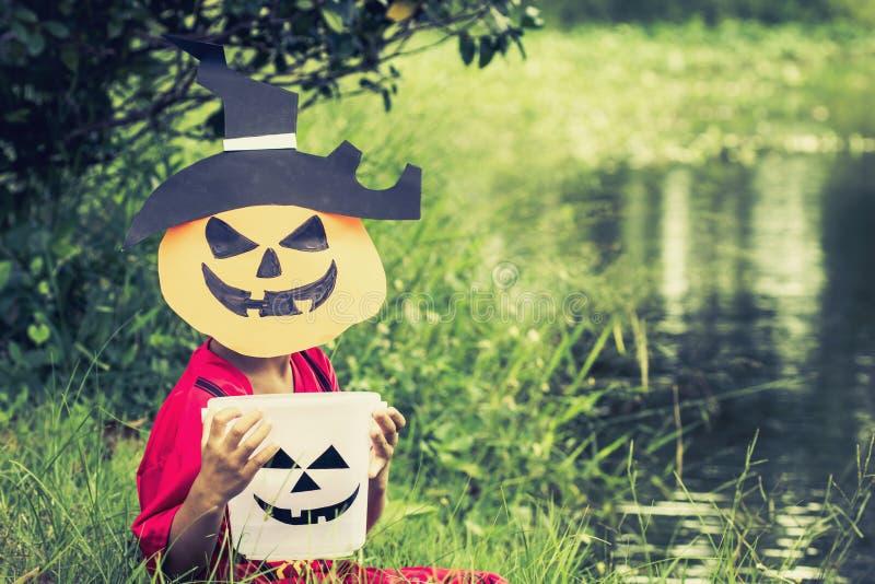 Fattiga ungar önskar godisen och spelar halloween med den handgjorda maskeringen arkivbilder