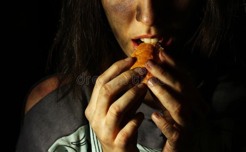 Fattigt smutsa ner flickan som äter en lappa av bröd arkivfoton