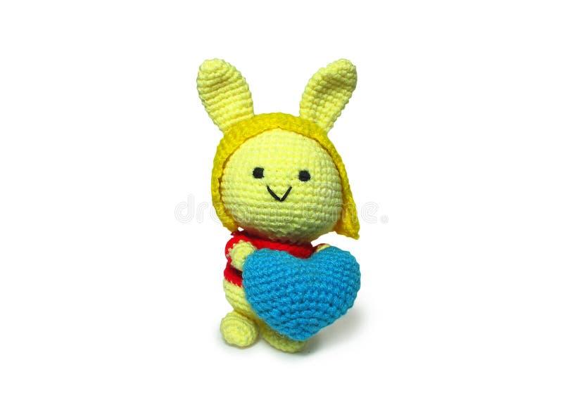 Fatto a mano sveglio lavora all'uncinetto la mano gialla della bambola che tiene il cuore blu con il percorso di ritaglio fotografia stock