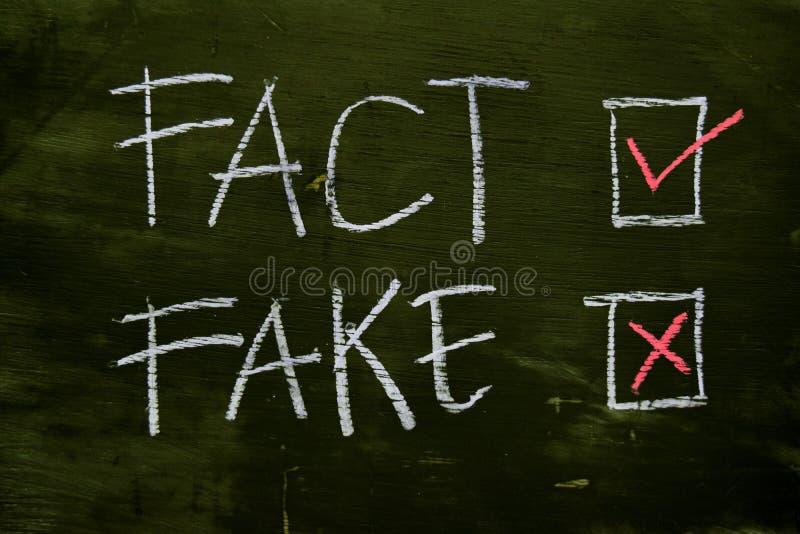 Fatto o falsificazione scritta con il concetto del gesso di colore sulla lavagna fotografia stock libera da diritti