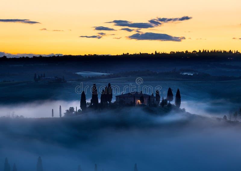 Fattoria della Toscana in foschia con i cieli gialli, d'Orcia di mattina di Val immagine stock libera da diritti