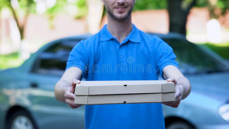 Fattorino amichevole che dà il contenitore di pizza, ordine dell'alimento online, servizio di ristorazione fotografia stock libera da diritti
