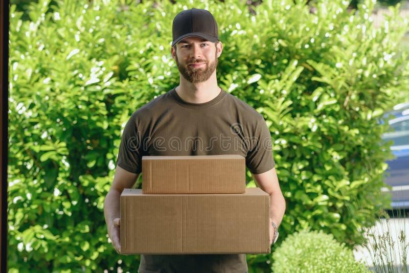 Fattorino bello con due scatole di cartone fotografia stock libera da diritti
